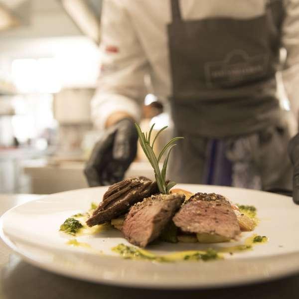 Kok serverer en lækker kødret på restauranten på Hotel Strandleben i Slesvig