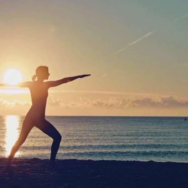 Kvinde dyrker yoga på stranden i Damp ved solnedgang