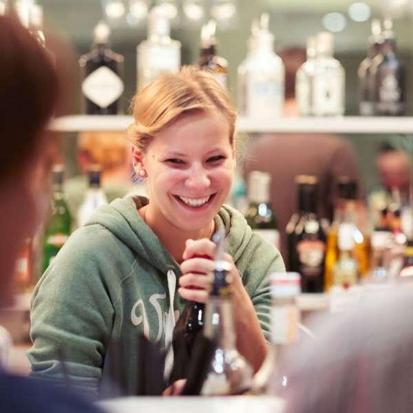 Kvindelig bartender åbner en flaske i baren på Beach Motel - Hotel i St. Peter-Ording