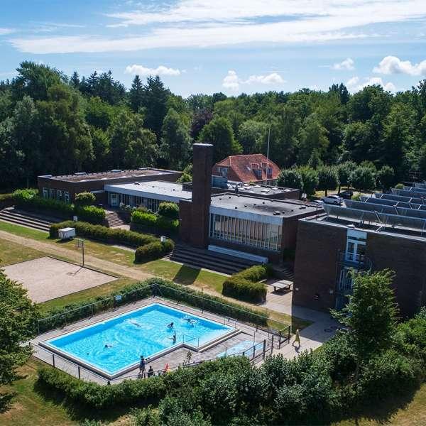 Lejrskole- og kursuscentret Christianslyst ved Sønderbrarup set bagfra med pool og haven i forgrunden
