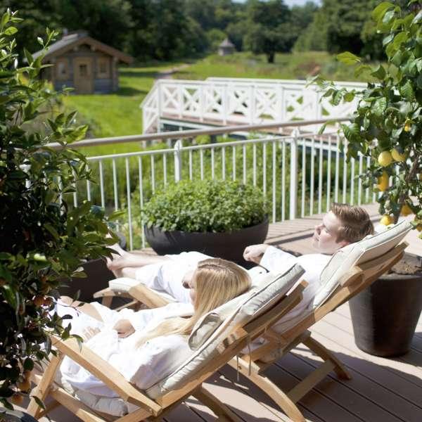 Par ligger i liggestol og nyder solen og udsigten over haven i spa-afdelingen på Hotel Waldschlösschen i Slesvig