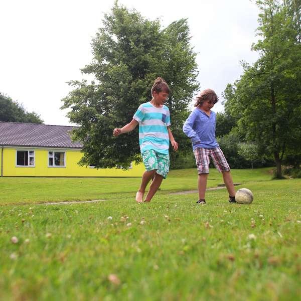 To børn spiller fodbold på græsplænen på vandrehjemmet i Borgvedel ved Slesvig