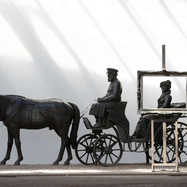 Hestevogn med portrætmaler i forgrunden på kunstudstillingen NordArt i Bydelstorp