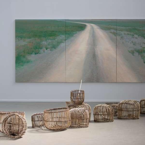 Installation med kurve og et maleri af en grusvej i baggrunden på kunstudstillingen NordArt i Bydelstorp
