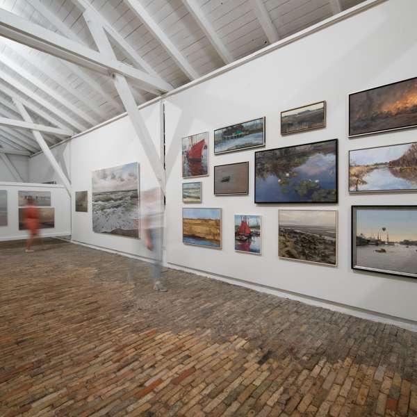 Malerier under taget med åbent træværk i loftet på kunstudstillingen NordArt i Bydelstorp