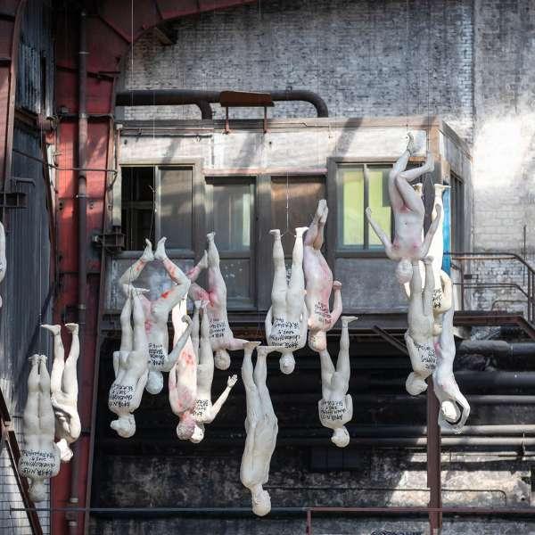 Menneskeskulpturer der hænger ned fra loftet fra fødderne på kunstudstillingen NordArt i Bydelstorp