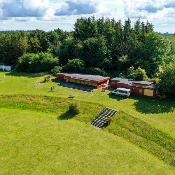 Mikkelberg Cricket Ground, klubhuset og hytterne set fra luften
