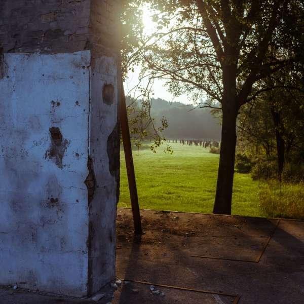 Rester af de historiske bygninger med jernstelerne i baggrunden på KZ-Gedenkstätte Husum-Schwesing