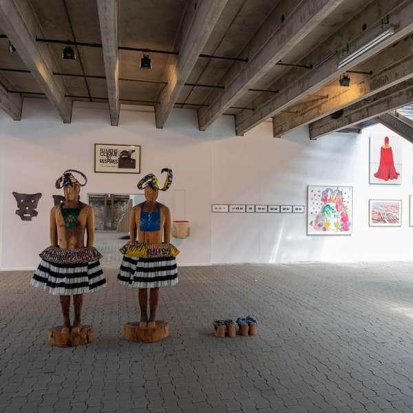 To skulpturer med andre kunstværker i baggrunden på kunstudstillingen NordArt i Bydelstorp