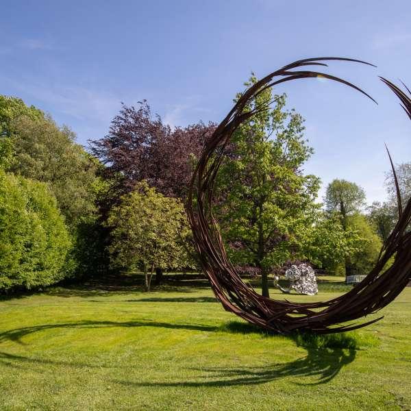 To skulpturer med træer i baggrunden i skulpturparken på kunstudstillingen NordArt i Bydelstorp