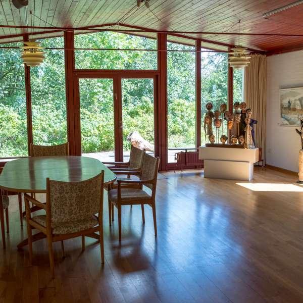 Udstillingslokale med hyggelige siddemuligheder på Mikkelberg - Nordisk center for kunst og cricket i Hatsted